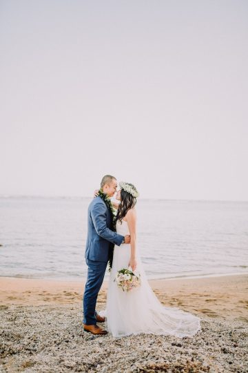 bride and groom kiss on beach