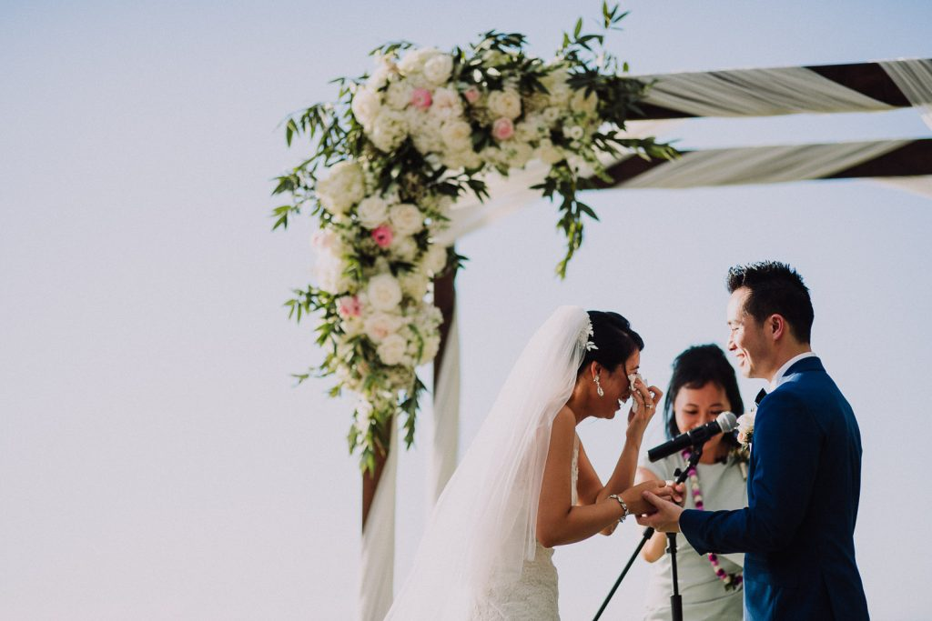 bride cries at ceremony with flowers on arch