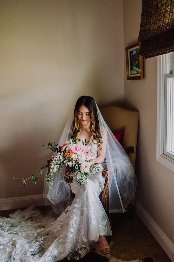 bride looking at bouquet of flowers in sunset ranch room