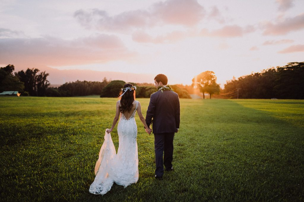 bride and groom walk into sunset at sunset ranch north shore hawaii