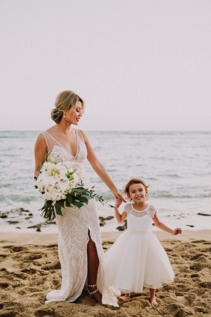 bride and flower girl on beach in hawaii