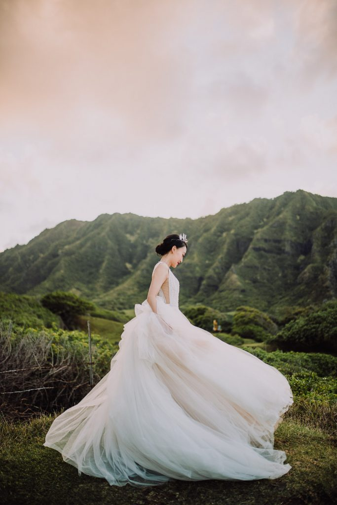 bride swirls wedding dress around in front of mountain at sunset