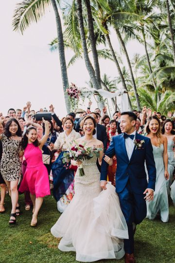 wedding guests laughing follow bride and groom to reception after ceremony