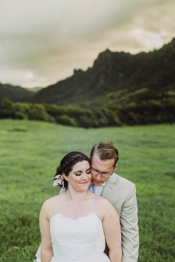 bride and groom in middle of field with mountains behind