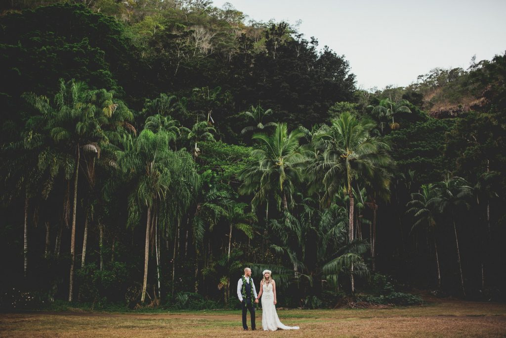 bride and groom stand in field with jungle behind them at sunset