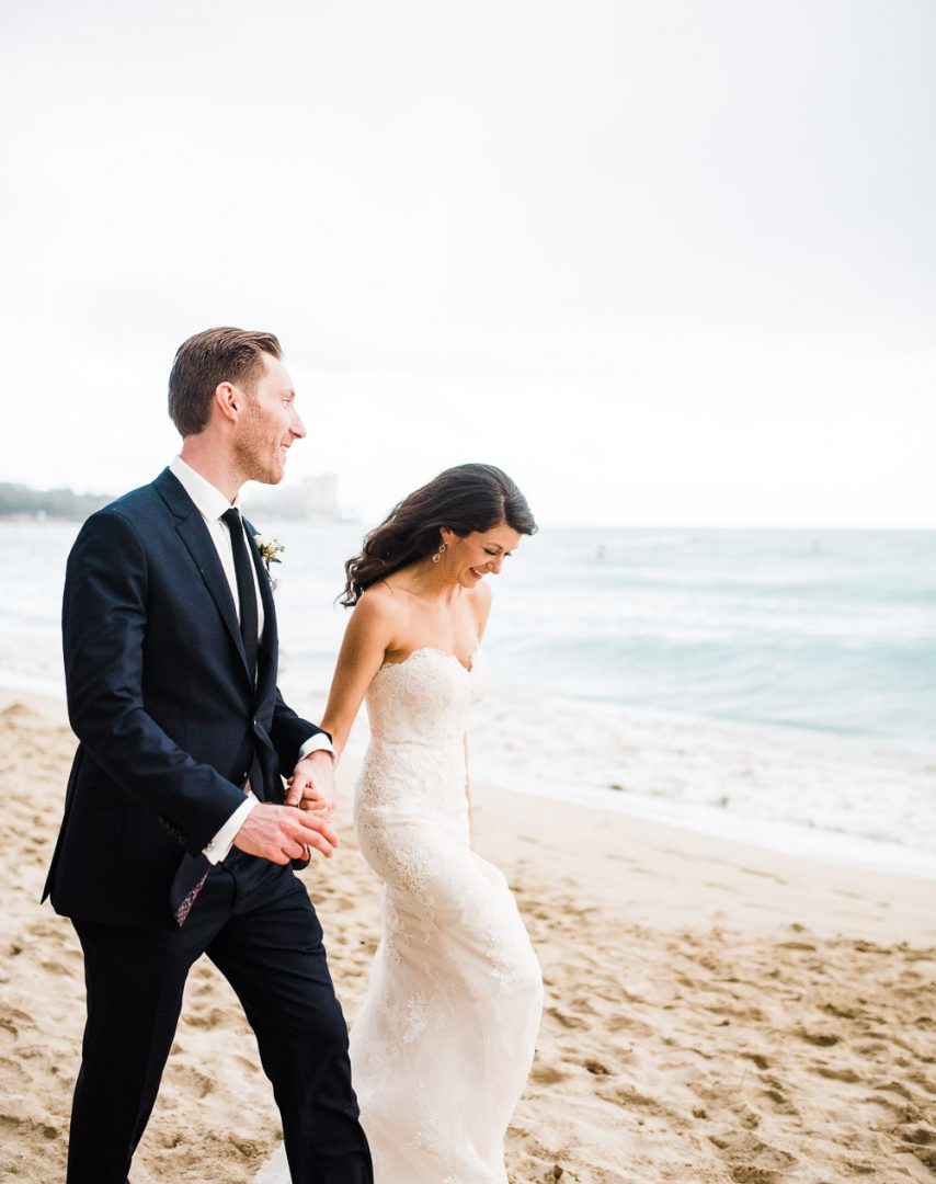 bride and groom walking on beach in Waikiki