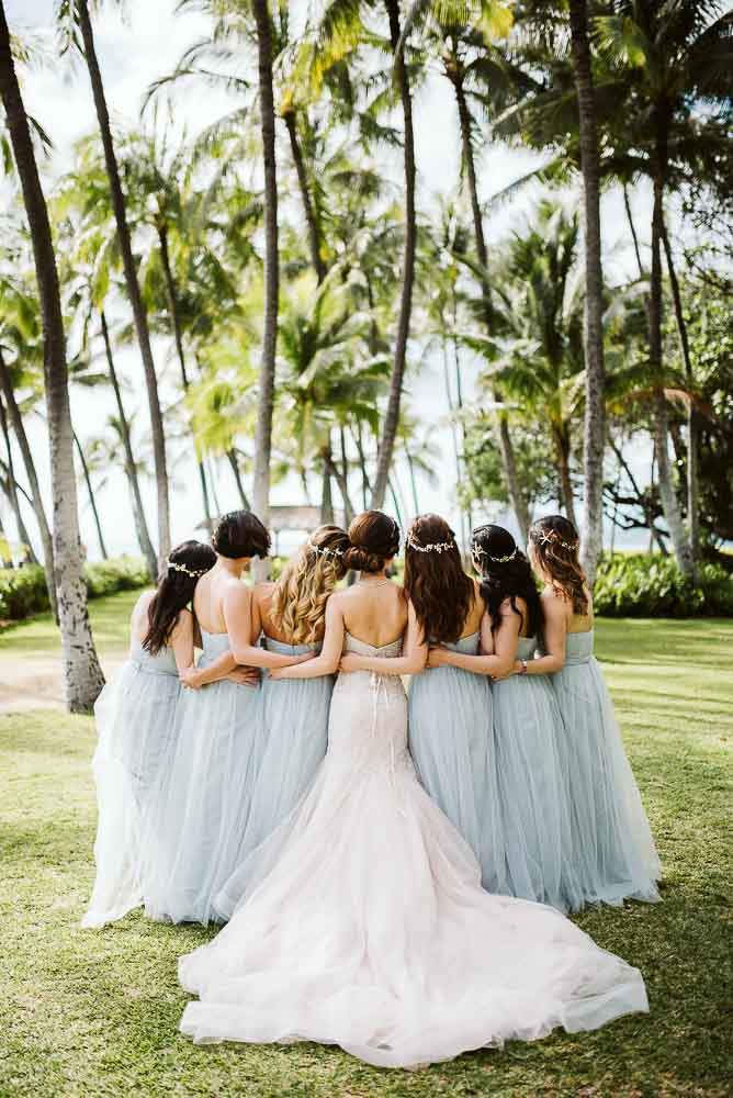 bride and bridesmaids hug infront on palm trees